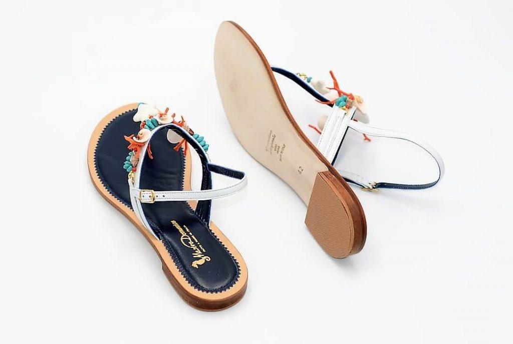 Weiße und blaue Sandalen mit Muscheln
